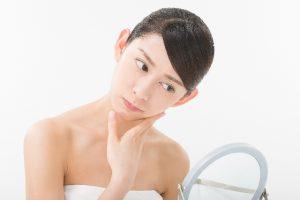 鏡をみて悩む女性