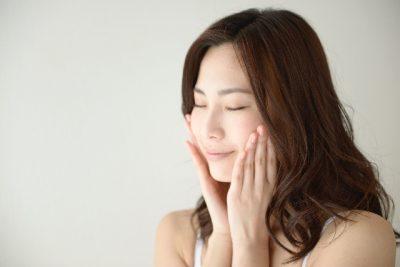 頬に手を当て目を瞑る女性の写真