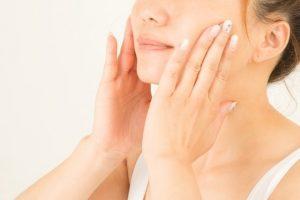 化粧下地を顔に塗る女性