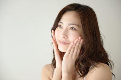 頬に両手をつけて微笑む女性の画像
