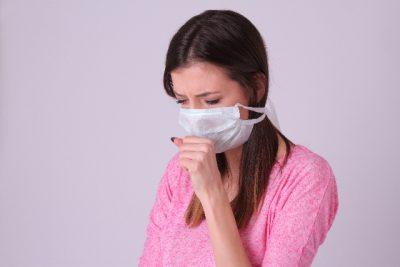 マスクをしてつらそうな女性の写真