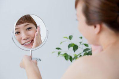 笑顔で手鏡を見る女性の画像