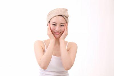 ヘアバンドをして手で顔を包む女性の画像