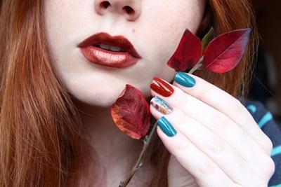 明るいメイクと手に秋の葉を持つ美しい女性