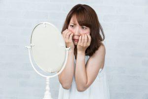 鏡を見て困っている女性の写真