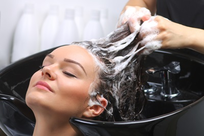 サロンで髪の毛を洗う女性