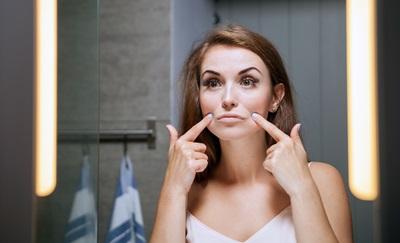 しわやほうれい線を気にして鏡を見ている女性