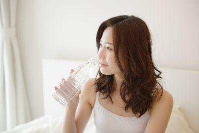 ベッドでお水を飲むロングヘアの女性