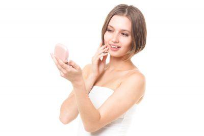 鏡を見て微笑む女性の写真