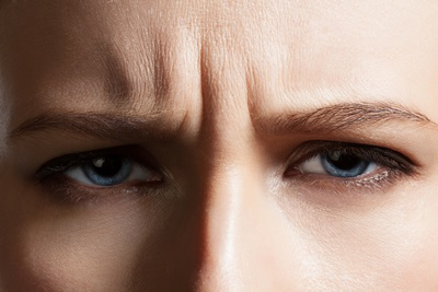 眉間にシワを寄せて正面を見つめる女性