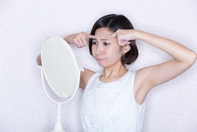 鏡を見て眉間のシワを気にしている女性