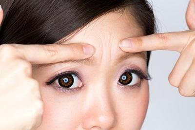眉間のシワを指さす女性