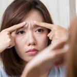 鏡で眉間のシワを指さす女性