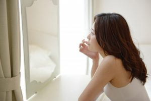 鏡を見て悩む女性の画像