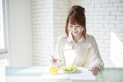 朝食をおいしそうに食べる女性