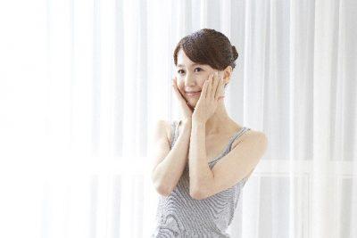 頬に触れて微笑む女性の写真