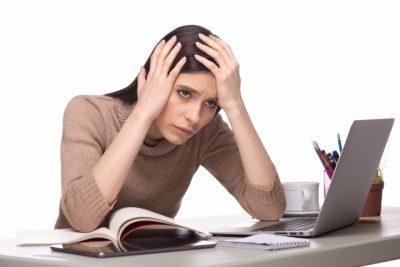 仕事中に頭を抱えて悩む外国人女性