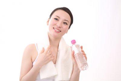 水を持って微笑むタオルを首にかけた女性