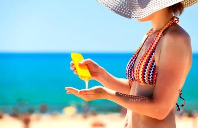 ビーチで日焼け止めを塗る女性