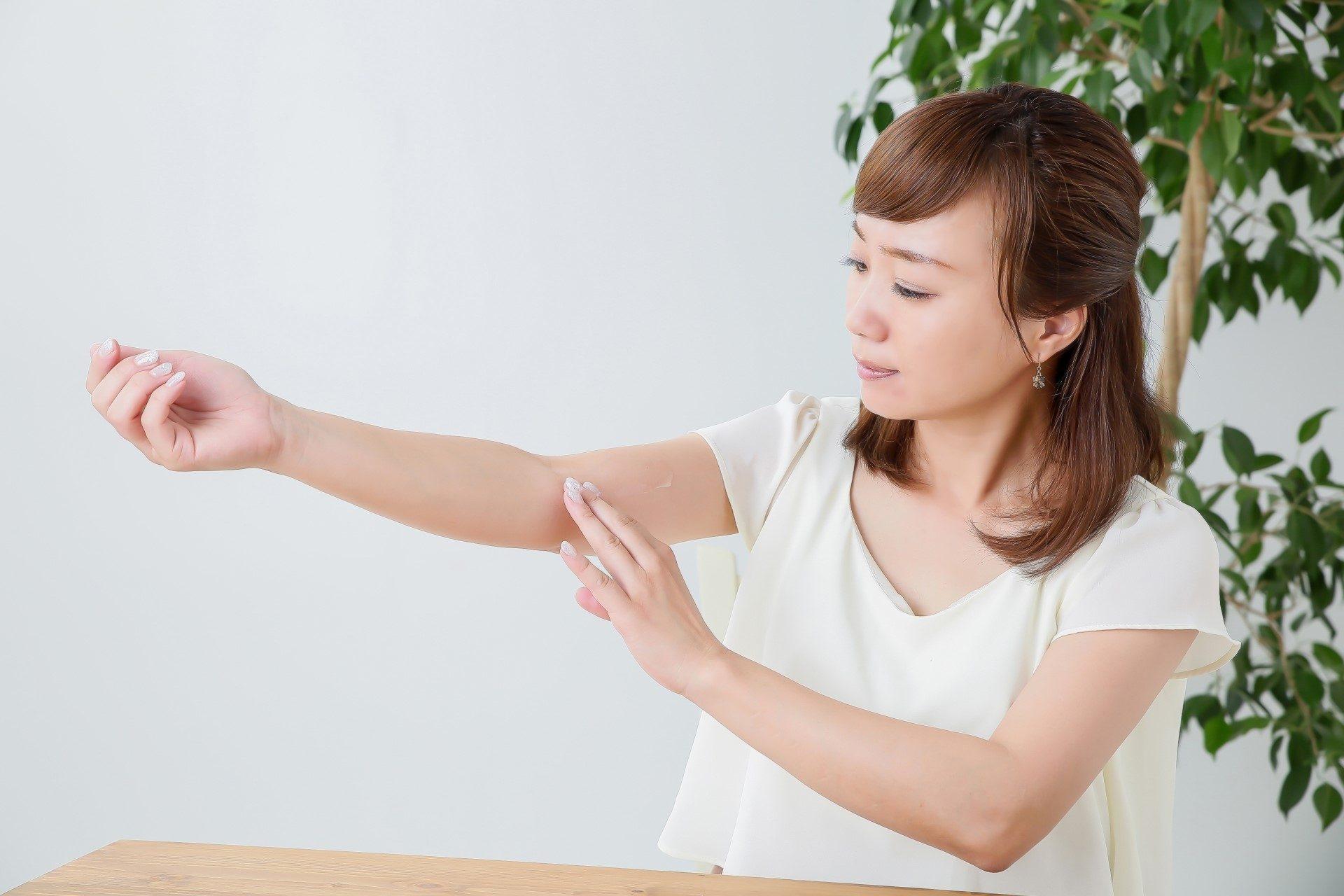 二の腕にクリームを塗る女性