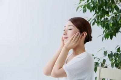 女性が頬を手で包み込んでいる画像