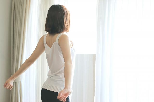 朝日を浴びながらのびをする女性