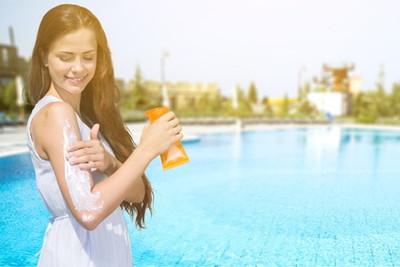 腕に日焼け止めを塗っている女性
