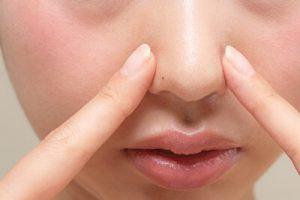 小鼻を人差し指で抑える女性