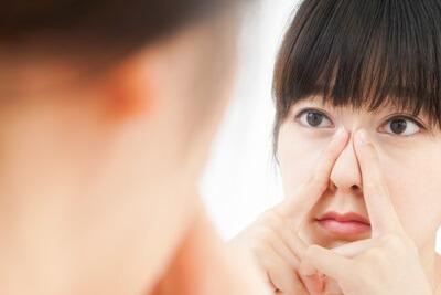 鏡の前で鼻の毛穴を気にしている女性