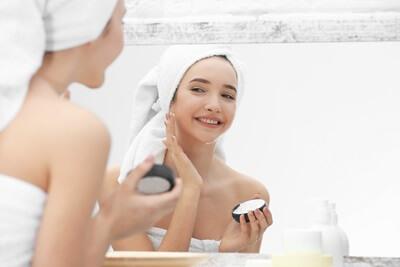 鏡でスキンケアをしている女性