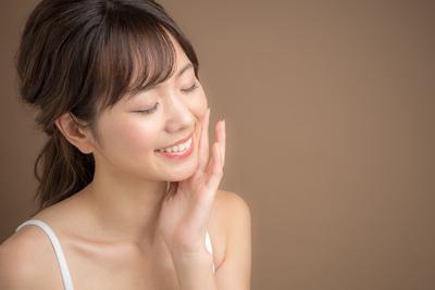 微笑みながら肌を触る女性