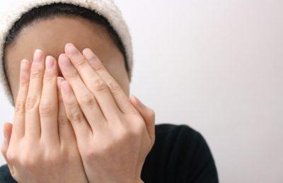 両手で顔を隠している女性