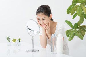 鏡を見つめる女性の画像