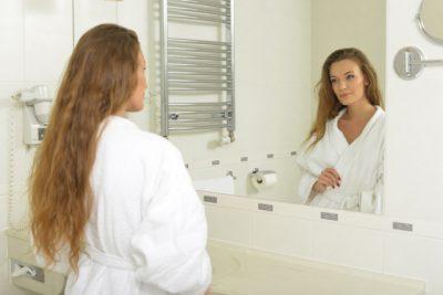 ホテルの洗面台で鏡をみる外国人女性