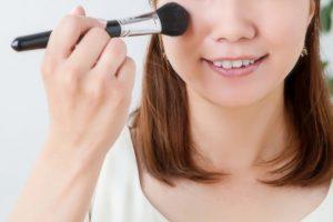 化粧品をブラシで頬にのせる女性