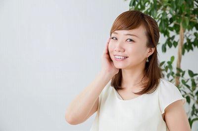 頬を抑えて微笑む女性