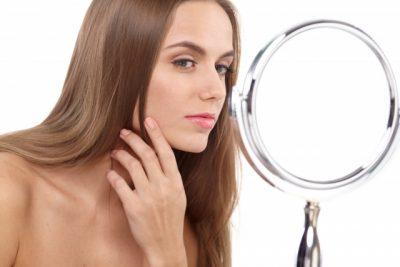 鏡で顔を見るロシア女性