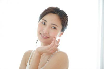 左頬に指を当て微笑む女性