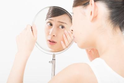 鏡を見て不安そうな女性
