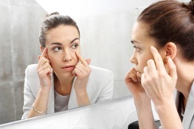鏡を見て目元のシワを気にしている女性