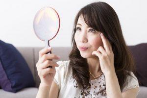 手鏡を持ち肌の状態と化粧をチェックしている女性