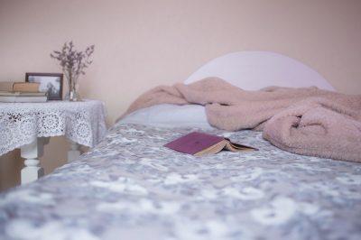 ベッドの上に本や毛布が散らばっている様子の写真