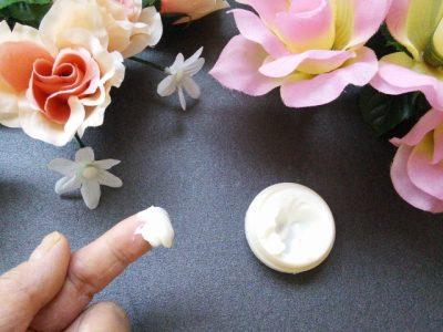花とクリームをとる指