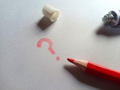 赤色のクエスチョンマークと赤鉛筆の画像
